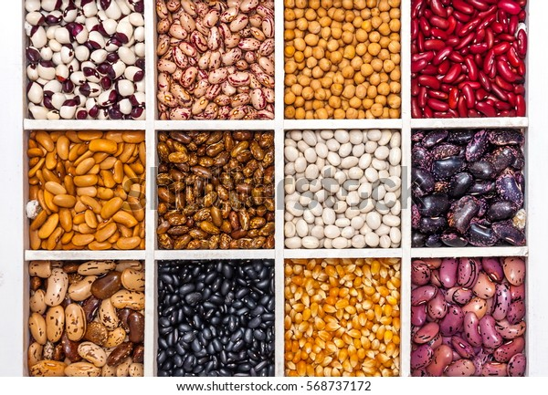 Variety of legumes, range, in a white wooden box with cells, peas, green peas, corn, haricot beans, lentils. View from above.
