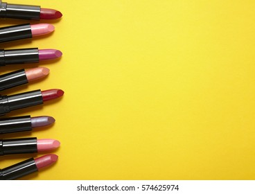 A variety of lipstick make up arranged on a bright yellow background with blank space at side