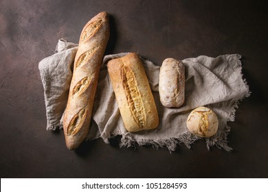 Variety of loafs fresh baked artisan white and whole grain bread on linen cloth over dark brown texture background. Top view, copy space.