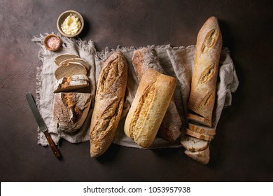 Variety of loafs fresh baked artisan rye, white and whole grain bread on linen cloth with butter, pink salt and vintage knife over dark brown texture background. Top view, copy space.