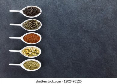 A variety of loose dried tea leaves on spoons (black, green, rooibos, chamomile and mate tea), photographed overhead on slate with copy space on the right
