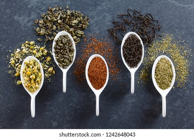 A variety of loose dried tea leaves on spoons (chamomile, green, rooibos, black and mate tea), photographed overhead on slate