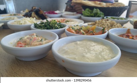 A variety of Middle Eastern cuisine starter salad hors d'oeuvre dishes closeup, Mediterranean kitchen, vegetable dish served in small plates in an Arabic restaurant. Tahini, hummus, cabbage, eggplants
