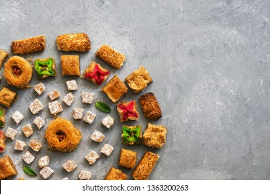 A variety of Middle Eastern sweets on a gray background. Arab dessert, baklava, lokum,cookies. Top view, flat lay, copy space