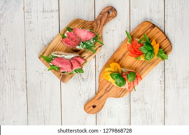 Variety of mini sandwiches with cream cheese, vegetables and salami. Sandwiches with cheese, tomato, salami, basil, on a light background, top view. Flat lay