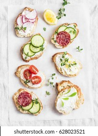 Variety of mini sandwiches with cream cheese, vegetables and salami. Sandwiches with cheese, cucumber, radish, tomatoes, salami, thyme, lemon zest on a light background, top view. Flat lay