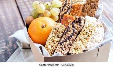 Variety Muesli bars and Fruits in cardboard box Healthy food