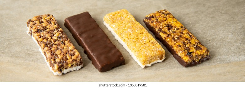 A variety of muesli and cereal bars. Different Energy protein bar on marble stone background. Set of energy, sport, breakfast and protein bars
