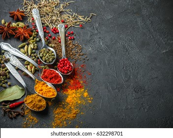Variety of natural spices, seasonings and herbs in spoons on the stone table - paprika, curry, coriander, cardamom,  rosemary, salt, pepper, cumin, chili, cinnamon, cloves, Top view with copy space