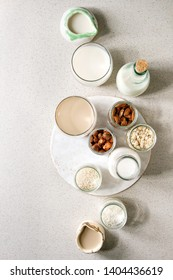 Variety of non-dairy vegan lactose free nuts and grain milk almond, hazelnut, coconut, rice, oat in glass bottles and ceramic jugs with ingredients above over white spotted background. Flat lay, space