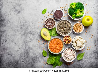 Variety of nutrient-rich food for vegans with copy space: beans, lentils, quinoa, tofu, vegetables, nuts, chickpeas, rice, avocado, fruit, stone background, top view. Healthy vegetarian nutrition