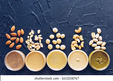 Variety of nuts butter in jars with ingredients. Homemade raw organic peanut, almond, cashew, macadamia and pistachio nuts paste on black background. Top view. Copy space.