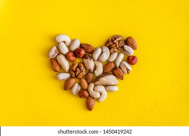 A variety of nuts are laid out in the shape of a heart on a yellow background. Flat lay. View from above. Copy space. The concept of health care, cardio, proper nutrition, healthy fats