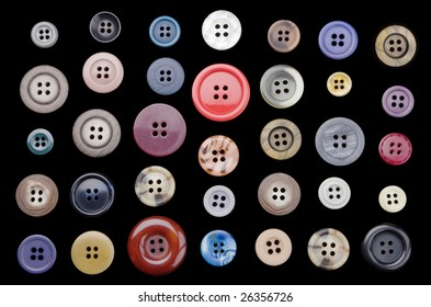 A variety of old buttons neatly arranged on a black background.