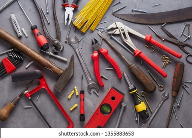 Variety of old vintage and modern household hand tools arranged as a flat lay still life on grey in a DIY and renovations concept