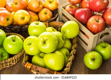 Variety of organic apples in baskets on wood table.
