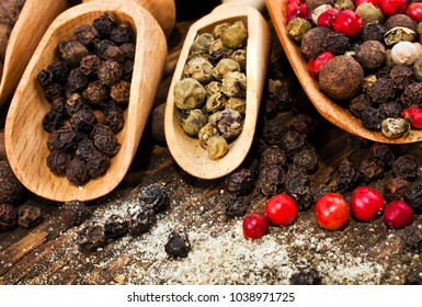 A variety of peppercorns in spoons on wooden background.