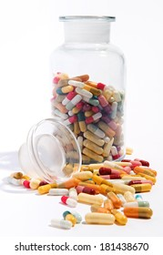 Variety of pharmaceutical capsules and pills lying on a white surface with an open half filled glass jar behind in a health care concept