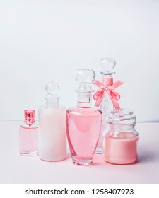 Variety of pink cosmetic product bottles and  flowers standing on white pink background with bokeh. Skin care, cosmetic shop, sale and abstract beauty concept.