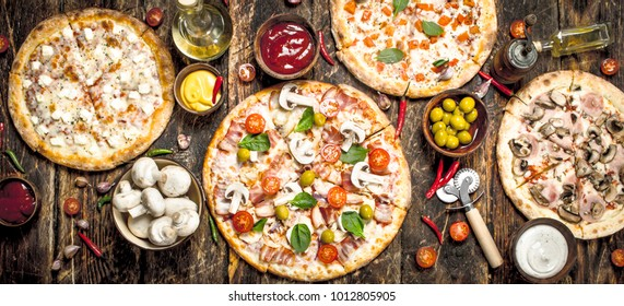 variety of pizzas. On a wooden background