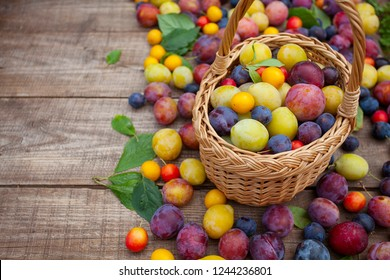 variety of plums on wooden surface