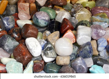 Variety of polished semi-precious stones, including amethyst, bloodstone, citrine, turquoise and sodalite, popular for energy healing, jewelry making and collecting.