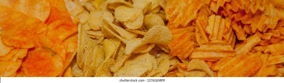 A variety of potato chips background. Background corrugated golden chips with texture.