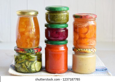 Variety of preserved food in glass jars - pickles, jam, marmalade, sauces, ketchup. Preserving vegetables and fruits. Fermented food. Autumn canning. Conservation of harvest