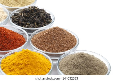 Variety of raw Authentic Indian Spices on square bowl isolated on white background. Focus on Cloves in full-frame.