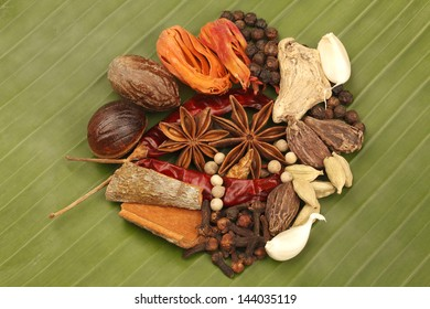 Variety of raw Authentic Indian Spices on green Banana leaf.