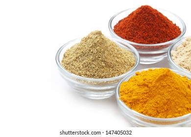 Variety of raw Authentic Indian Spices Powder on glass bowl isolated on white background in full-frame.