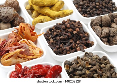 Variety of raw Authentic Indian Spices on square bowl on white background.