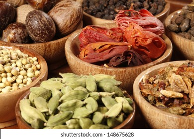 Variety of raw Authentic Indian Spices on wooden bowl.
