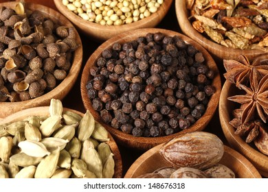 Variety of raw Authentic Indian Spices on wooden bowl in full-frame.