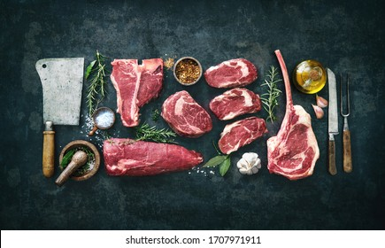 Variety of raw beef meat steaks for grilling with seasoning and utensils on dark rustic board