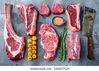 Variety of raw beef meat steaks for grilling with seasoning and utensils set, tomahawk, t bone, club steak, rib eye and tenderloin cuts, on gray stone background, top view flat lay