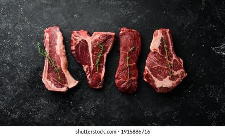 Variety of raw black Angus Prime meat steaks: t-bone, striploin, Rib eye, new york steak. Top view. On a stone background.