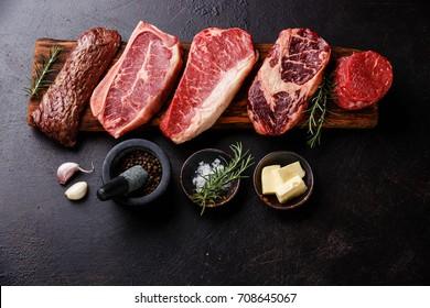 Variety of Raw Black Angus Prime Fleisch Steaks Machete, Blade on bone, New York, Rib eye, Tenderloin Filet Mignon auf Holzbrett und gewürzt