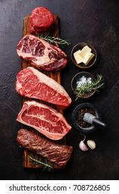 Variety of Raw Black Angus Prime meat steaks Machete, Blade on bone, Striploin, Rib eye, Tenderloin fillet mignon on wooden board and seasoning