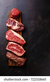 Variety of Raw Black Angus Prime meat steaks Machete, Blade on bone, Striploin, Rib eye, Tenderloin fillet mignon on dark background copy space