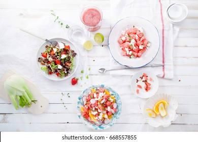 Variety of raw fresh summer salads with fruits and berries on white wooden background served with napkins and drinks. Summertime organic easy lifestyle concept. Flat lay with copy space.