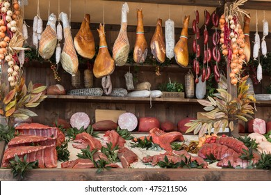 Variety of Raw Meat and sausages in Butcher Shop on Wooden Board