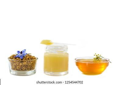 variety of raw organic honey bee products board surrounded by flowers on white