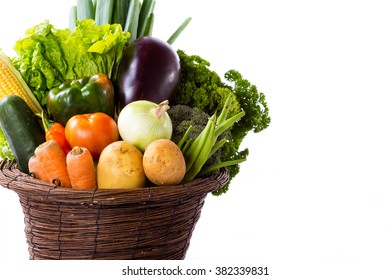 Variety of raw vegetables in basket isolated on white background