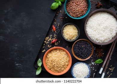 Variety of rice - red, black, basmati, whole grain, long grain parboiled and arborio - in bowls. Overhead view