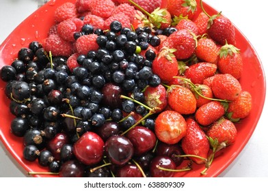 variety of ripe berries on the red plate - strawberry, raspberry, blackberry, cherry