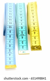 Variety of rulers for sewing: blue, cyan and yellow tapes for measuring, isolated on white background