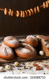 Variety of rye bread on a wooden background with milk, a bundle of bagels, flour, grain and quail eggs