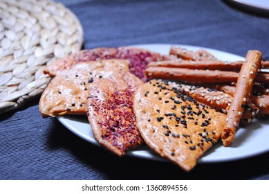 variety of salty pastry with black seed, sesame, and sumac on gray plate with dark background and hay. salty crackers salty biscuits close up