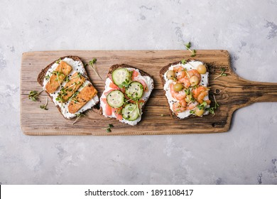 Variety of sandwiches for breakfast, snack, appetizers - tempeh, salmon, prawns grilled whole grain bread sandwiches with microgreens on a light background